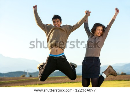 Young couple holding hands jumping outdoors.