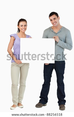 Young couple holding sign against a white background