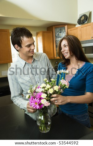 Young couple in kitchen arranging flowers in vase.