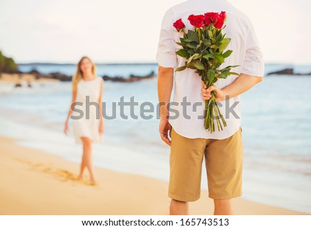 Young couple in love man holding surprise bouquet of - Boy propose girl with rose image ...