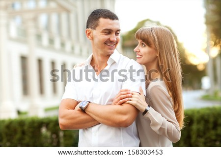 Young couple in love outdoor. They are smiling and looking at each other.
