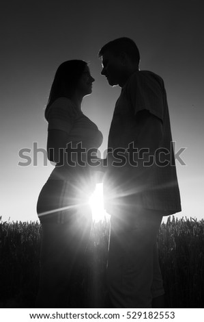 Young couple in love standing in the wheat field on sunny summer day.