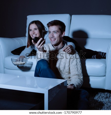 Young couple in love watching TV at night