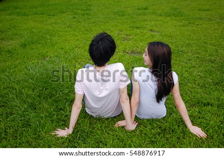 Young couple in the park back sitting on the grass