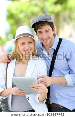 Young couple in town using electronic tablet