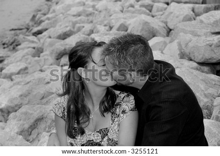 young couple kissing on a rocky beach