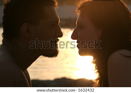 young couple looking at each other on the sunset beach
