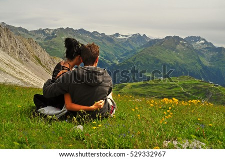 Young couple looking at  mountains / Pretty couple in love standing in nature and relaxing / Lovers embracing in beautiful nature landscape