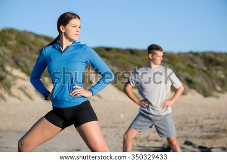 Young couple of man and woman stretching on ocean beach