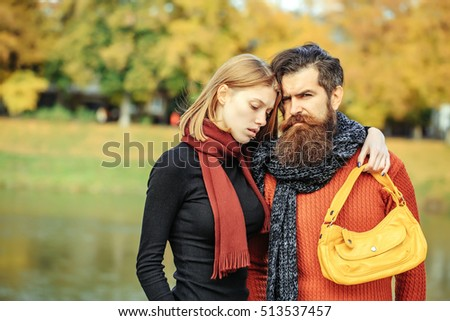 Young couple of pretty girl and bearded man hipster with scarfs and yellow bag outdoors in park on autumn day on natural background