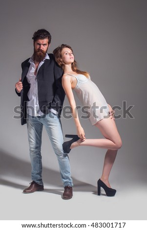 young couple of sexy slim woman in underwear and shoes with handsome bearded man has beard in jacket on grey studio background