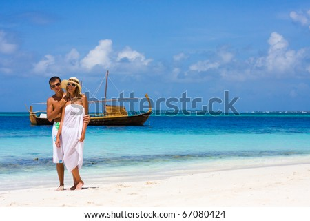 Young couple on a beach on a background a yacht