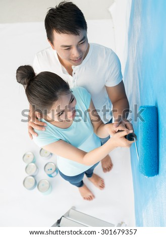 Young couple painting wall at home, view from above