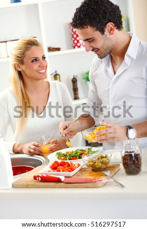 Young couple prepare vegetable salad for lunch.They are standing by the kitchen table.