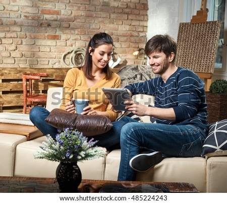 Young couple sitting at home on sofa, using tablet computer, smiling.