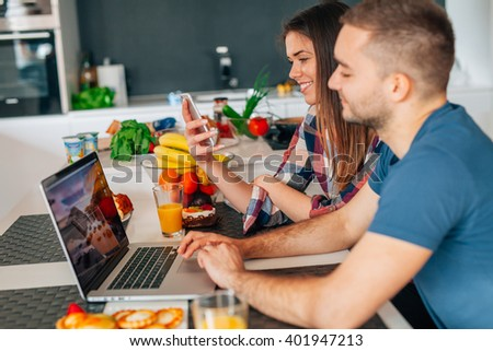 Young couple sitting in the kitchen. Man is using laptop. Girl is using smartphone