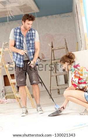 Young couple sweeping in house under construction, man holding brush, woman holding shovel.