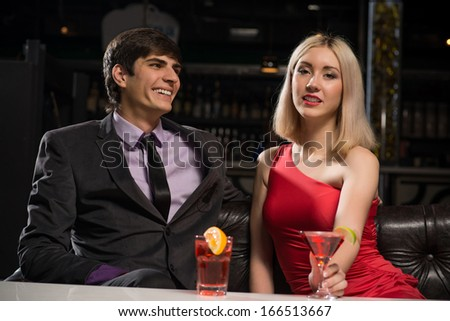 Young couple talking in a nightclub, have fun