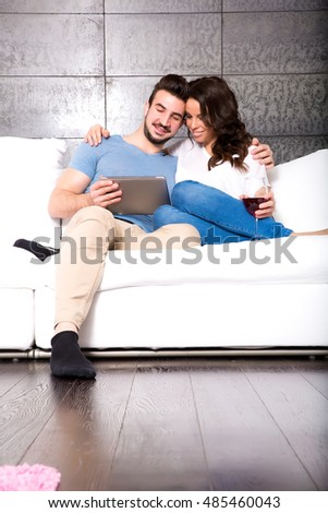 Young couple using a Tablet PC together on the Sofa at home.