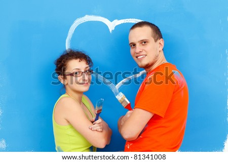 Young couple with a heart painted on the wall