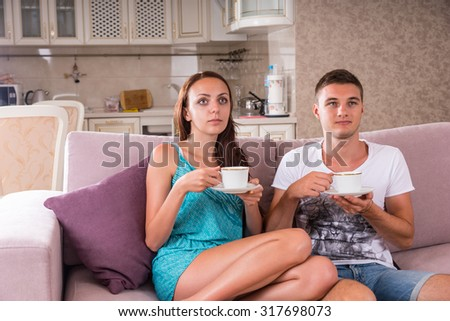 Young Couple with Mugs of Coffee or Tea Sitting on Sofa Together and Watching Television with Blank Expressions