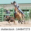 Young cowboy on a horse competing in calf roping during a rodeo. - stock photo