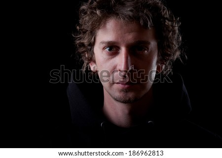 Young curly hair caucasian man wearing black hooded sweatshirt. Low key portrait taken on black background.