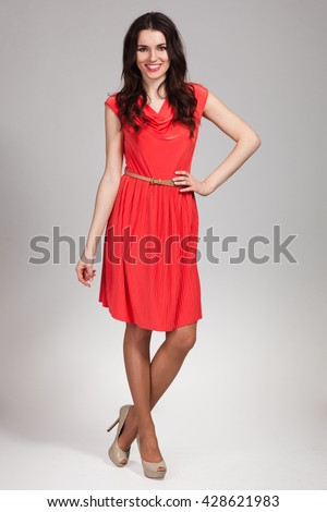 Young cute woman posing in red dress