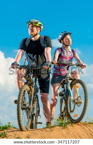 Young cyclists on mountain covered rays of sun