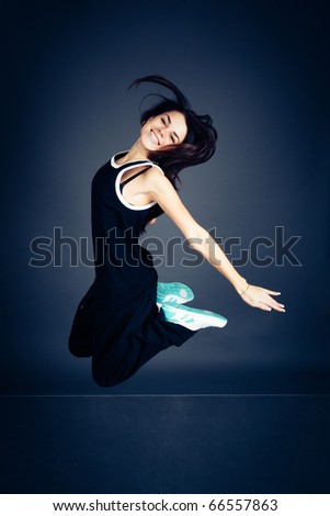 Young dancing woman in black suit on dark background