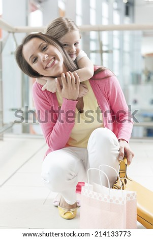 Young daughter hugs mother in shopping mall