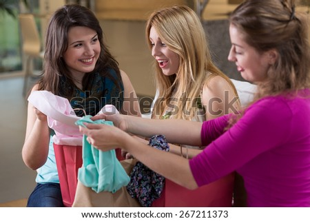 Young delighted woman and her friends looking at new clothes