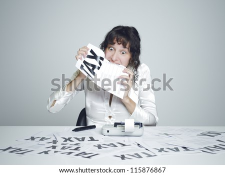 Young desperate woman at her paperwork covered desk biting a tax form