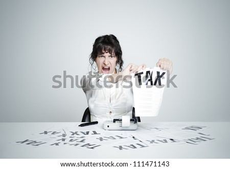 Young desperate woman at her paperwork-covered desk ripping up a tax form staring at the camera