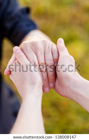 Young doctor hold elderly hands