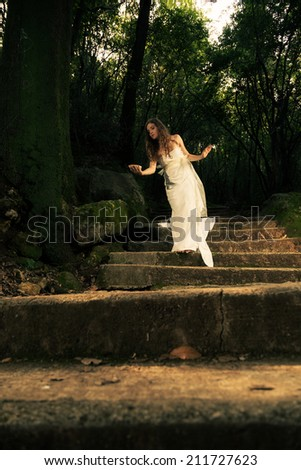 Young dreamy woman dressed in white walking in the forest - processed colors, soften effect