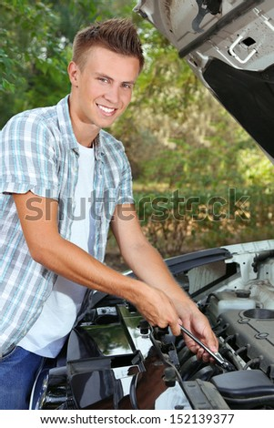 Young driver repairing car engine outdoors