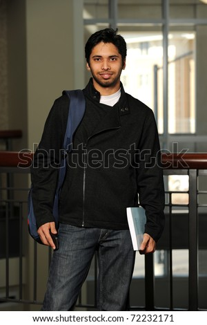 Young Eastern student holding a book inside a College building