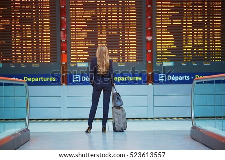Young elegant business woman with hand luggage in international airport terminal, looking at information board, checking her flight. Cabin crew member with suitcase.