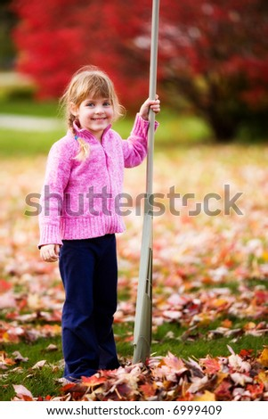 Young elementary girl pausing by a pile of leaves she's just raked.