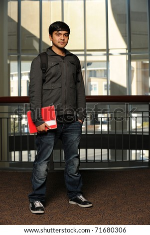 Young Ethnic Student standing holding a copybook with college building as background