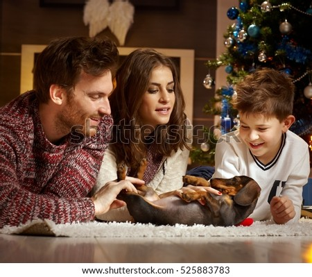 Young family caressing dachshund puppy received for christmas, all smiling.