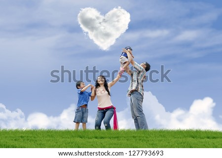 Young family is having fun under heart shape clouds in the park