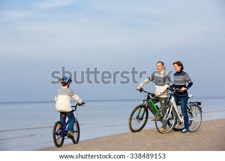 Young family of three riding bicycles on sand beach