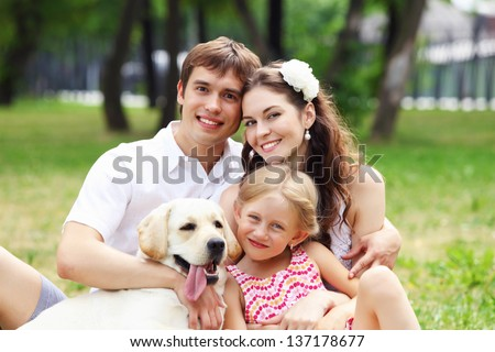 Young Family Outdoors in summer park with a dog