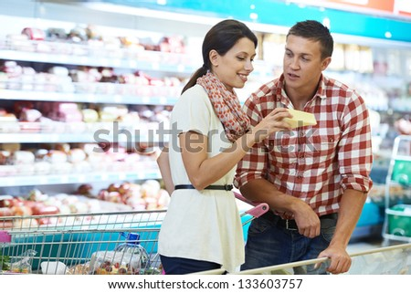 Young Family people choosing bio food cheese in grocery supermarket during weekly shopping