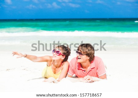 young family sitting on beach and having fun, caribbean
