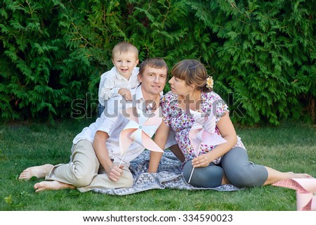 Young family sitting on the grass in a park with toys.