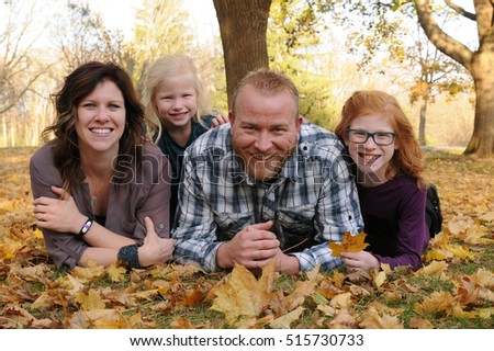 young family smiling in colorful fall leaves
