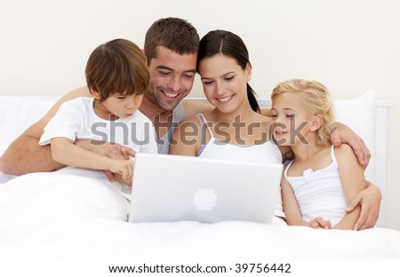 Young family using a laptop in bed
